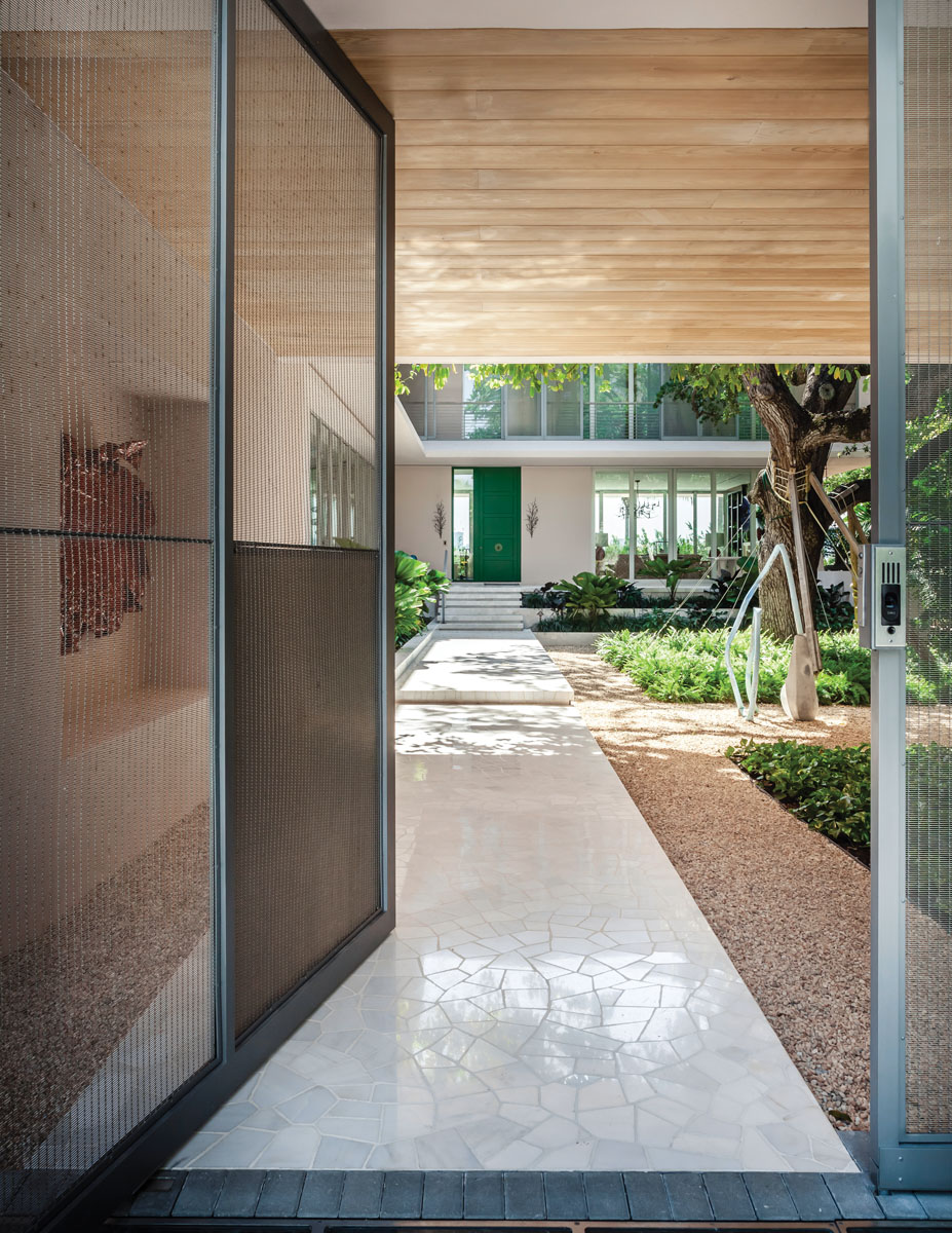 The front gate is designed as a screen, offering a glimpse into the inner courtyard, terraces and gardens. Broad overhangs protect the interior from the sun, where the modern architecture provides a clean canvas that caters to the homeowner's love of art.