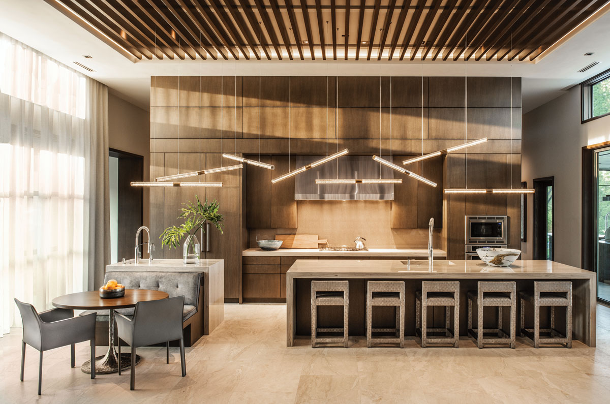 Busby's oak slab cabinetry is managed to perfection in the kitchen. Custom light pendants by Shakúff reflect off the gleaming island topped in quartzite. Tucking Vanguard counter stools beneath the island and choosing contemporary chairs for the breakfast nook bring this space its modern edge.