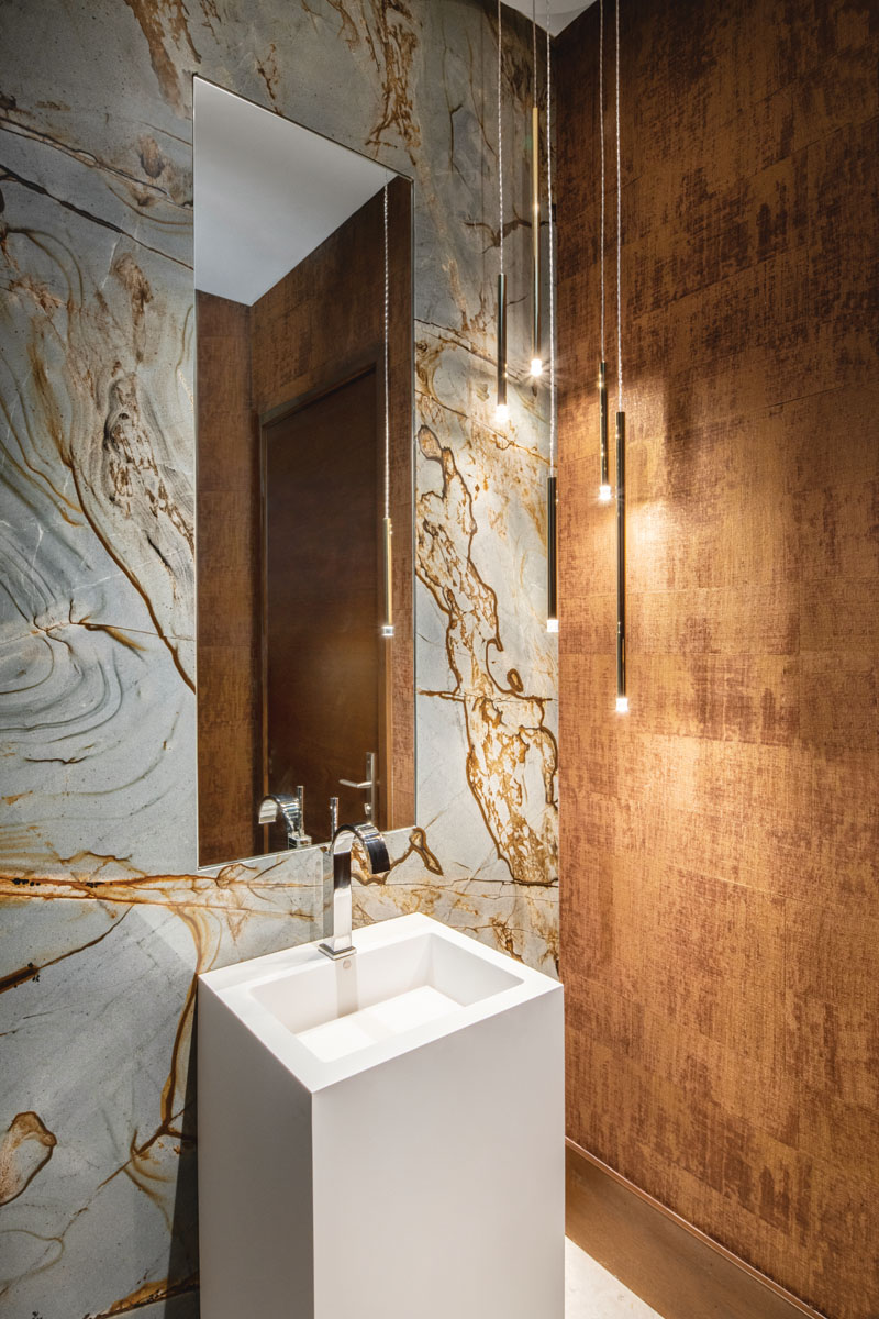 In the powder room, a modern MTI pedestal sink with a Newport Brass faucet present as clean-lined elements against the sumptuous veining of the quartzite stone wall and Phillip Jeffries' wall covering with its rich patina. Studio Italia pendants illuminate the space styled with a custom inset mirror.