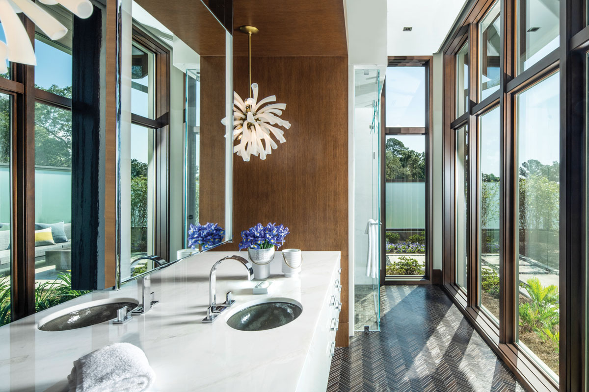 In the master bath, an Arteriors light fixture blossoms, while Busby's wood panels and Walker Zanger's interlocking wood tile flooring create a warm backdrop for the Bianco Rhino marble countertop.