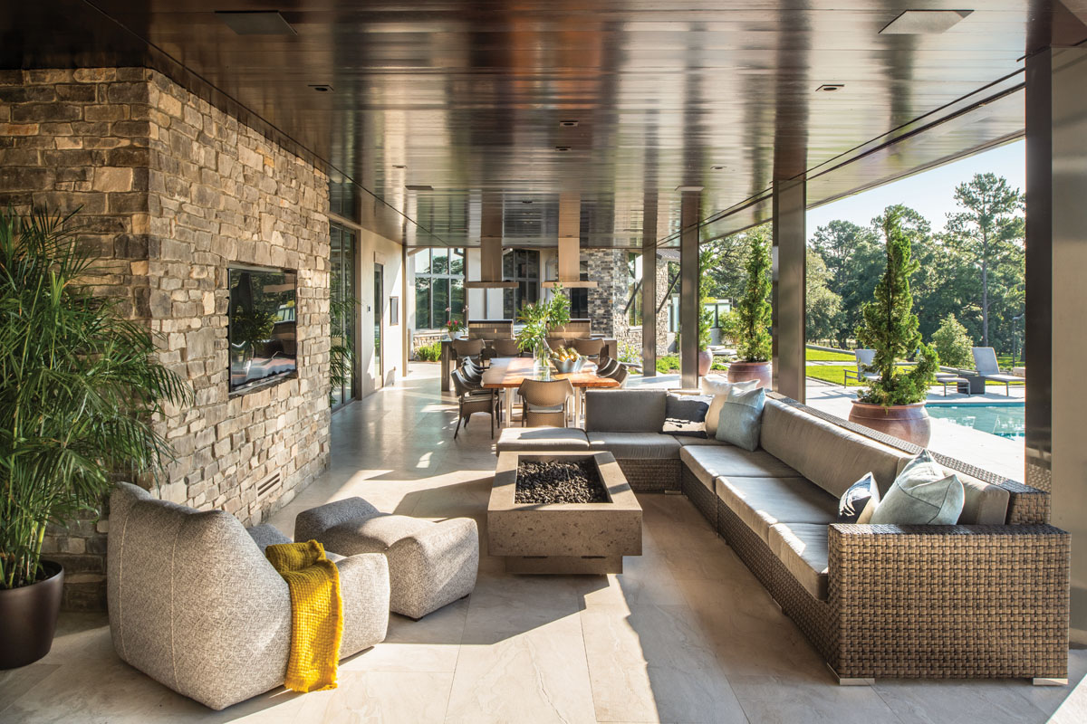 The screened lanai, where a Janus et Cie sectional wraps around RH Modern's fire table, was built for entertaining. Beyond, a custom dining table designed by Ansana and Qui Studios provides ample space for the Martins' dinner parties.