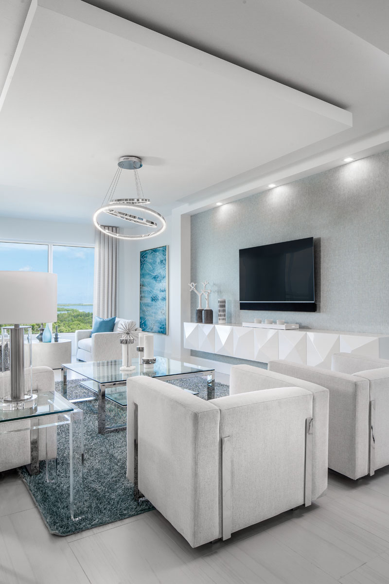 "A custom, white-lacquer floating console lines the wall in the living room. Elan's polished chrome chandelier styled with three LED bracelets of concentric sizes appears to dance above Sunpan's seating centered by Bernhardt's glass-topped cocktail table. ""The blue painting, Rhapsody, matches the beauty of the outdoor views,"" interior designer Elizabeth Manchego says."