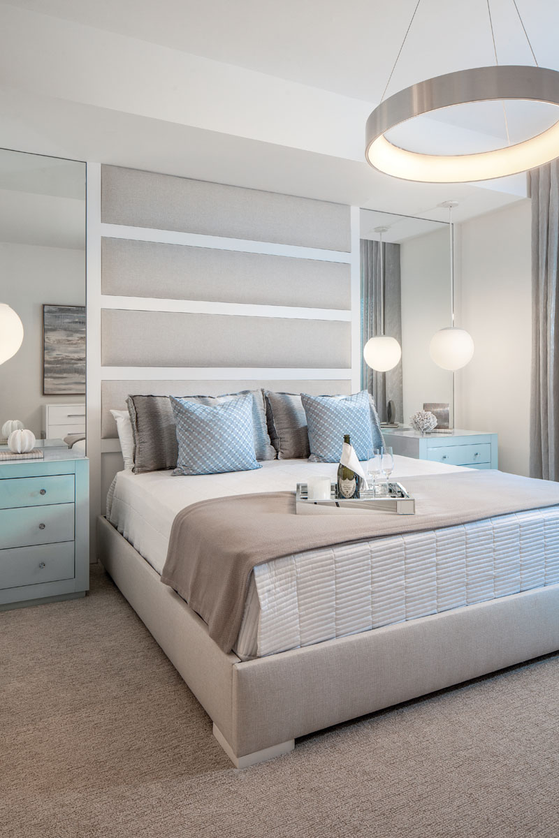 "A custom, upholstered headboard wall provides a focal point in the master bedroom, where spa-blue painted bedside chests from Worlds Away are reminiscent of sea glass. ""WAC Lighting's ""Corso"" chandelier became the jewel of the room like a bracelet,"" Manchego says."