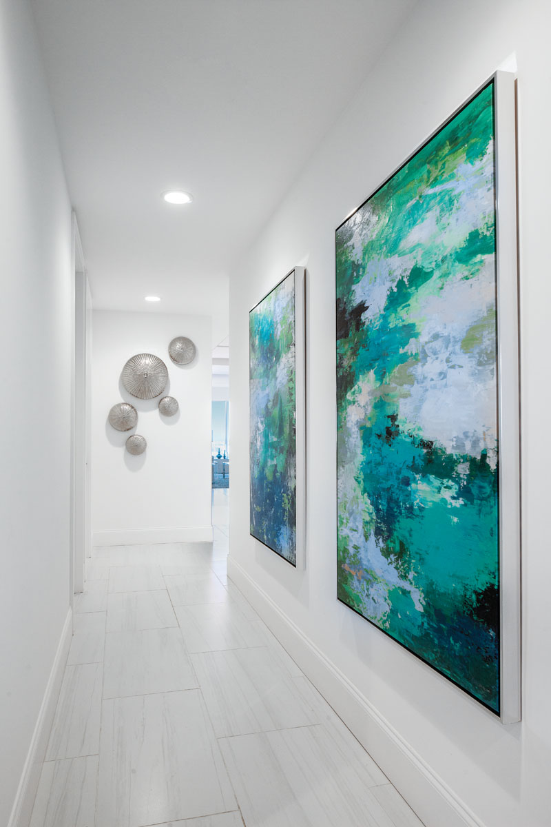 Inspired by sea urchins, metal sculptural discs from Global Views dot the wall of the hallway, where ocean hues that color Leftbank's art pieces lead the eye through to the private spaces.