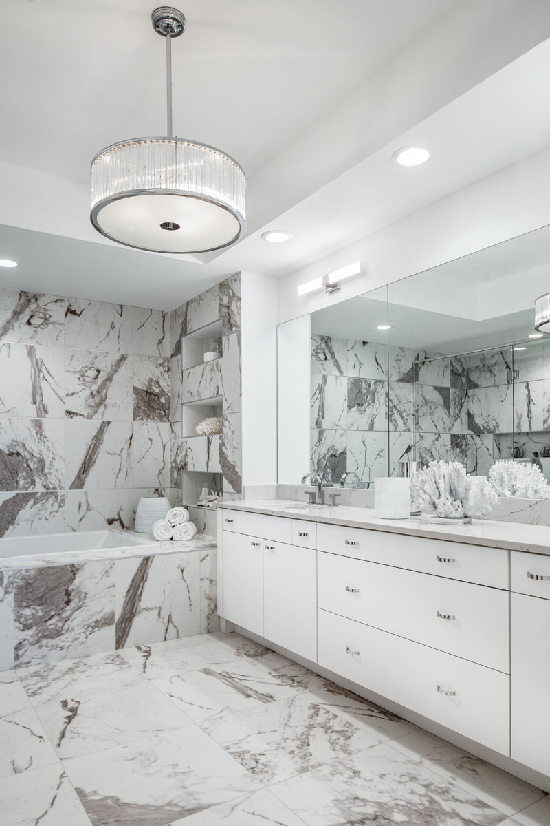 In the master bath, Brizo's white vanity from Ferguson features functional, flat-paneled storage cabinets with the drawer detail to create visual interest. The surrounding veining offers contrast. While simple, the space looks elegantly dramatic.