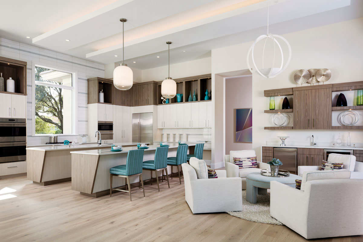 "Wildwood's vintage-inspired, milk glass ""Subway"" light pendants cast a soft glow around the kitchen lined with SouthLinks' crisp custom cabinetry. Turquoise counter stools from Design Master Furniture sit in bold and colorful complement to a cocktail ottoman that centers the nearby lounge area. Here, Century club chairs swivel to join conversation in the kitchen on one side and the living room on the other."