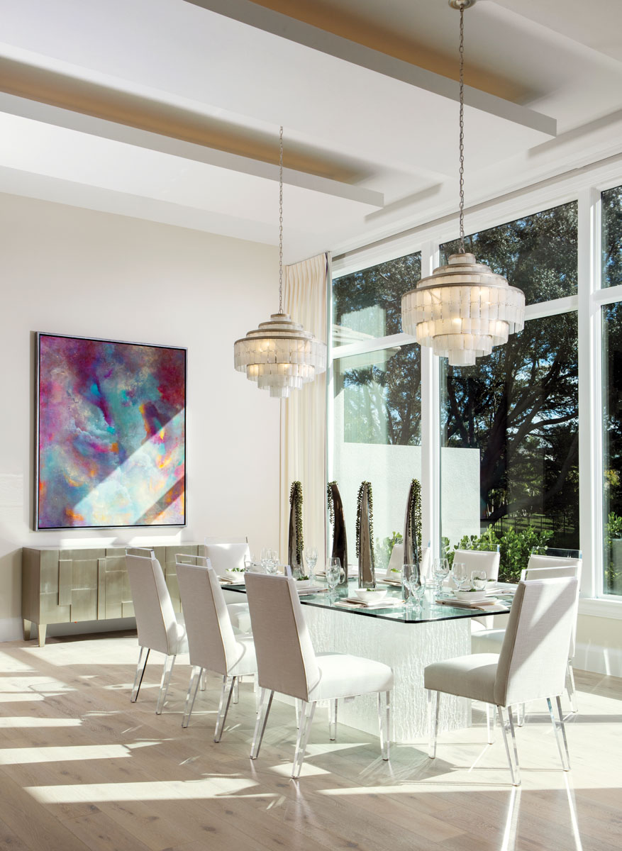 "Framed windows capture picturesque views from the dining room, where a pair of Currey & Company chandeliers shimmers above Bernhardt's glass-topped table with its ""Artic"" base. Design Master's ""Hollywood"" chairs sparkle and shine with acrylic top rails and tapered legs, while a painting commissioned by a local artist creates colorful contrast."