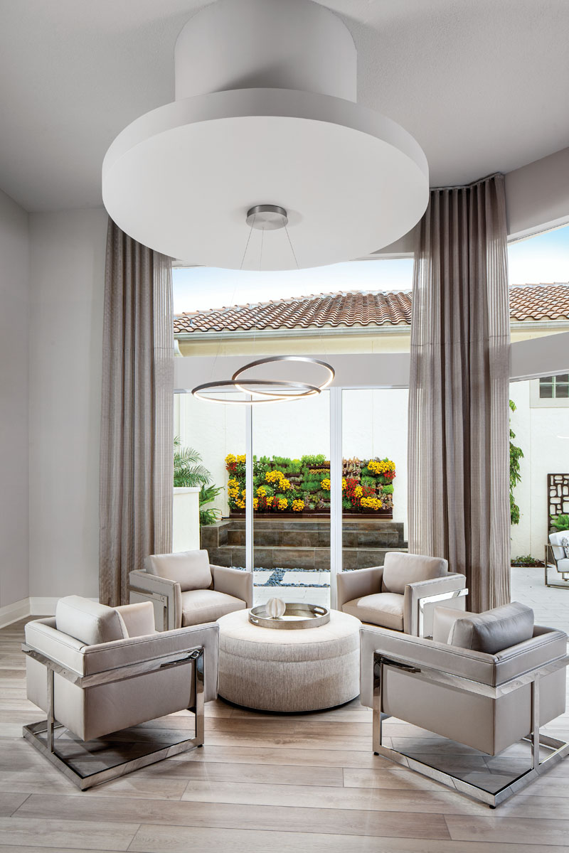 The sitting area, which overlooks the living wall in the tranquil courtyard, serves as the home's headquarters. Thayer Coggin's taupe-leather armchairs shape an intimate gathering space around the upholstered cocktail ottoman from Vanguard.