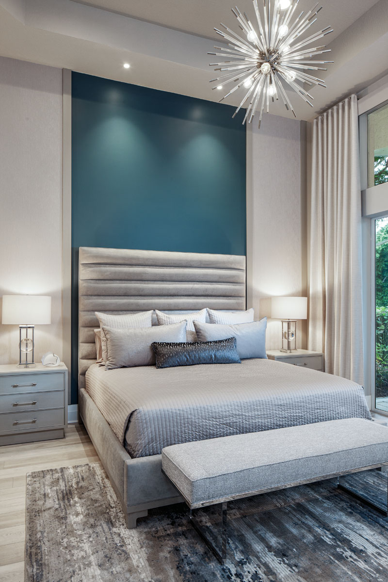 "Adding a touch of drama, the master bedroom is lighted by the ""Andromeda"" starburst pendant from Wilson Lighting. An acrylic and polished-chrome Bernhardt bench covered in faux linen rests at the foot of Vanguard's upholstered bed."