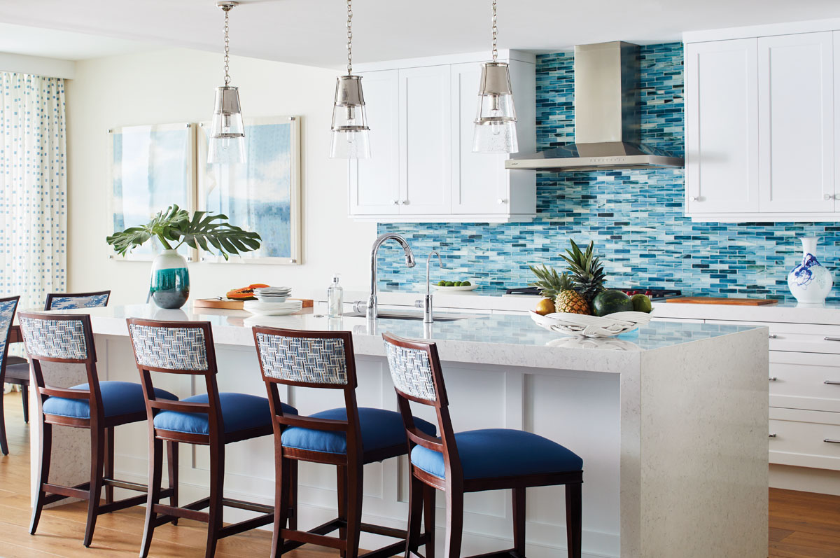 A custom, tile backsplash that displays the owners' penchant for blue and white anchors the kitchen. Here, Visual Comfort's clean, conical pendants revive nautical hurricane globes above a man-made porcelain, waterfall-edge island lined with Hickory Chair's dark wood counter stools backed in a textured print from Kravet.