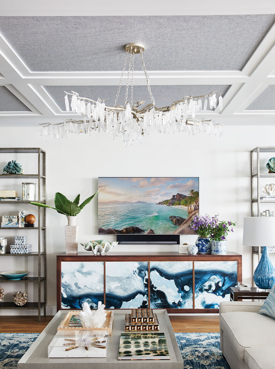 The living area's custom console is a collaboration between John Strauss Furniture and Black Crow Studios wallpaper. Interior designer Lisa Kahn customized the piece by blending the walnut case with the watercolor wave in navy and white.