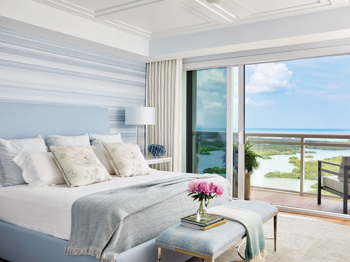 """Scalamandré linens pull open to a calming Gulf view from the master bedroom, where the lines of Thibaut's blue, linen mesh grasscloth, """"Sandia,"""" wrap the walls and imbue the space with an ethereal feel. Arteriors' glass lamp appears to float above a Hickory Chair bedside table, while the Bernhardt bench anchors the bedstead. Loloi's area rug swaddles the private space in comfort."""