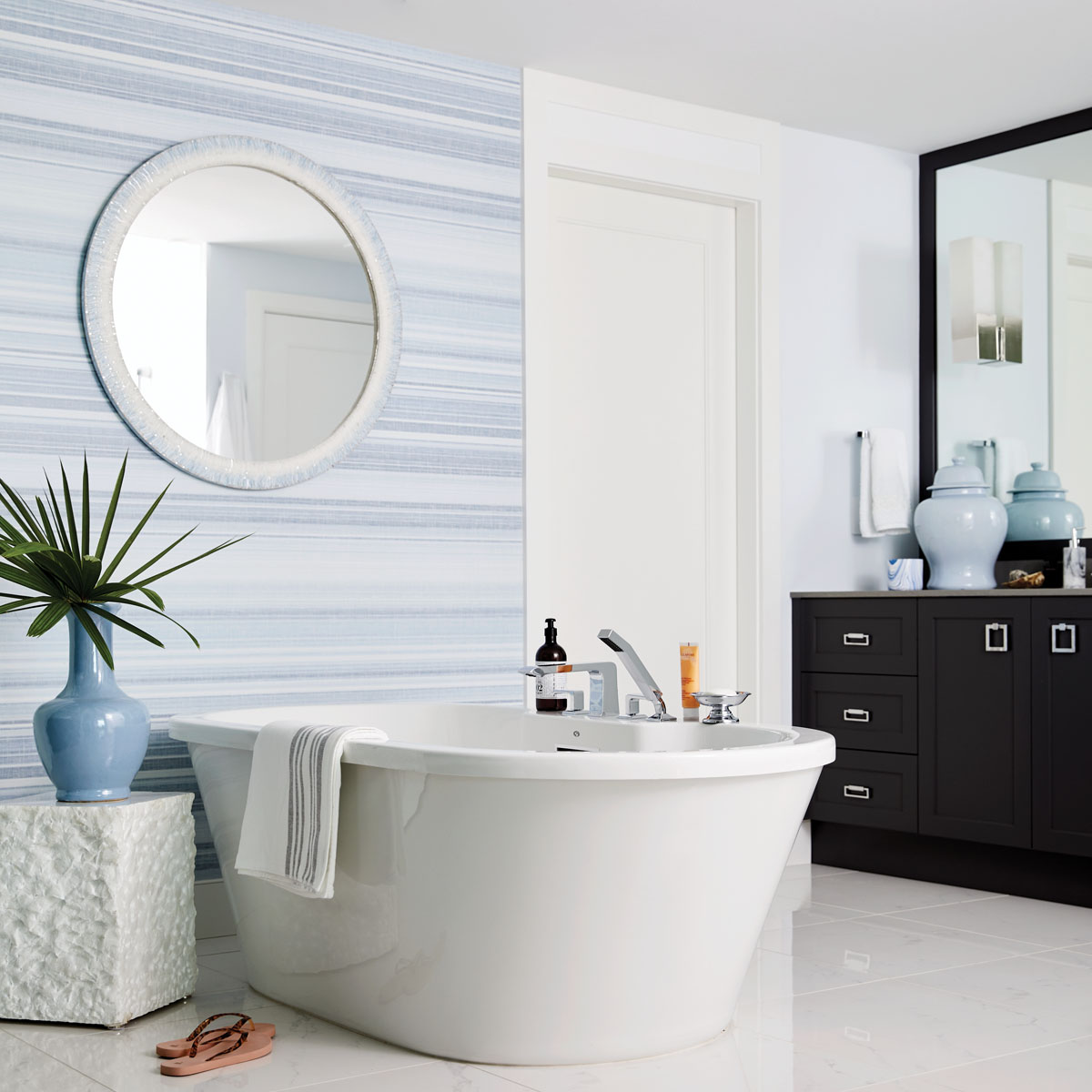 Ercole Home's mirror dots the wall in circular contrast to the soothing lines of Thibaut's wall covering that unifies the master bedroom with its en suite bath. Here, the Van Cleve Collection vase on Bungalow 5's accent table adds a touch of nature to the otherwise subdued palette.