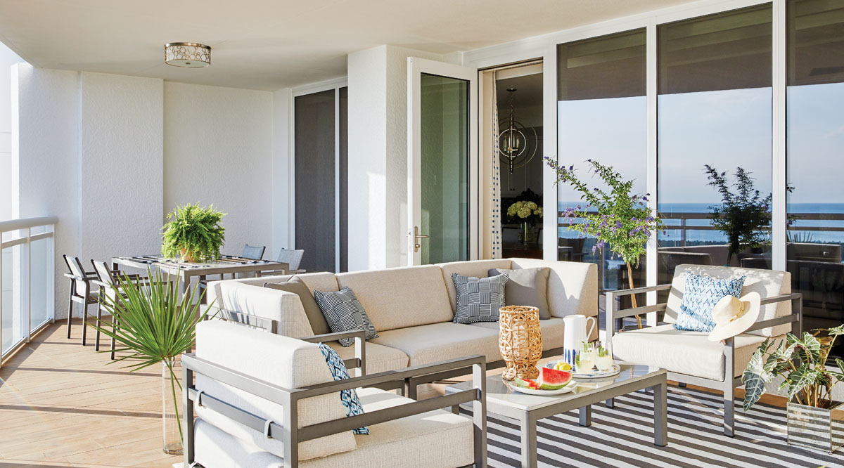 Glass doors open to extend the indoor living spaces out to the balcony. The orchestrated palette echoes the colors and textures found in the sandy beachside landscape. An array of Pavilion furnishings shapes the open-air social spaces anchored by an awning-striped Dash & Albert area rug.