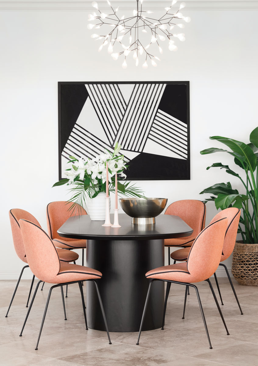 "In the dining area, shapely Gubi ""Beetle"" chairs in an Osborne & Little terracotta wool encircle the ebony stained oak table in geometric contrast to the black-and-white abstract by artist Jaime Derringer via Minted."