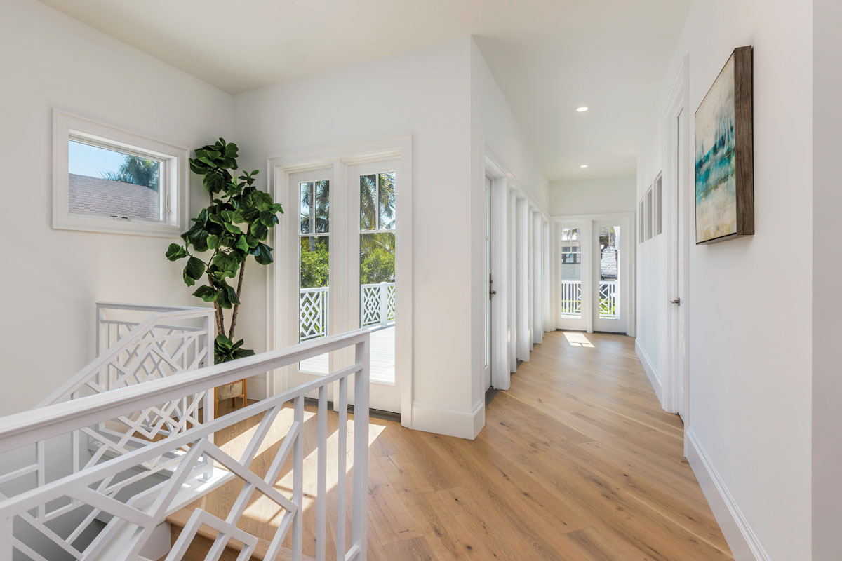 The stairway leading to the second-floor's three en suite guest rooms features white-washed railings that echo the coastal-cottage charm of the exterior architecture.