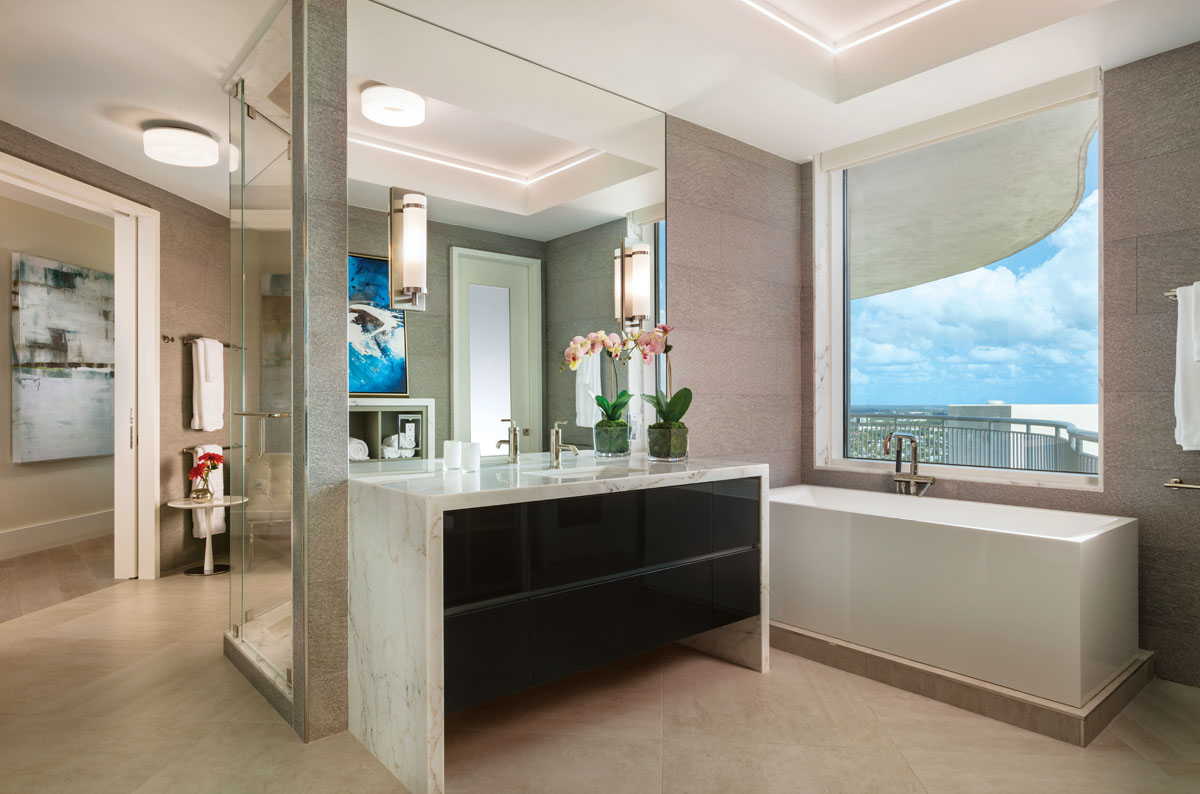 A sparkling, minimalist aesthetic prevails in the master bath, where a Nokori tub by BainUltra, purist fixtures by Kohler, a floating vanity with individually lit drawers, and Porcelanosa's modern large-format porcelain flooring creates a relaxed spa-like aura.