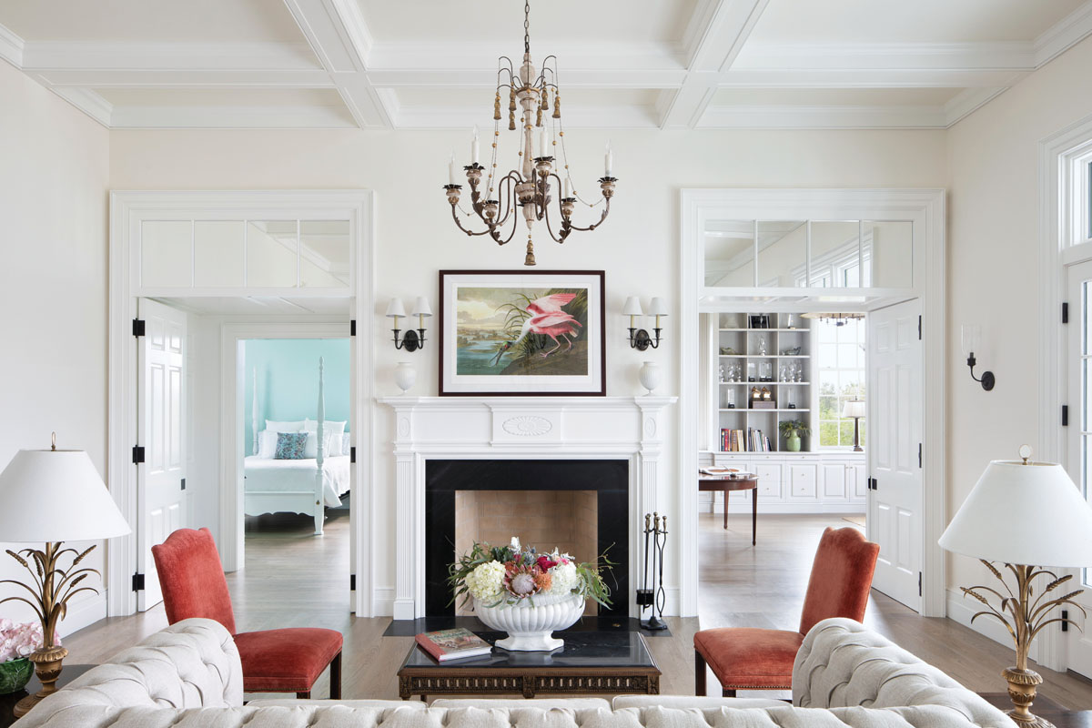 Plush furnishings float against a cloud of white in the living room, where wall lamps from Circa Lighting flank the fireplace. Glimpses of a ground-level guest suite, left, and the music room, right, offer clues to the Georgian floorplan.