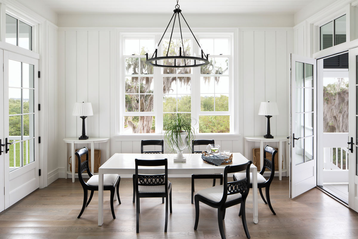 Cascading sunlight floods the breakfast room through unadorned windows that frame picturesque views. Capitol Lighting's iron ring chandelier is paired with an eclectic array of period furnishings while remaining true to the understated monochromatic palette.