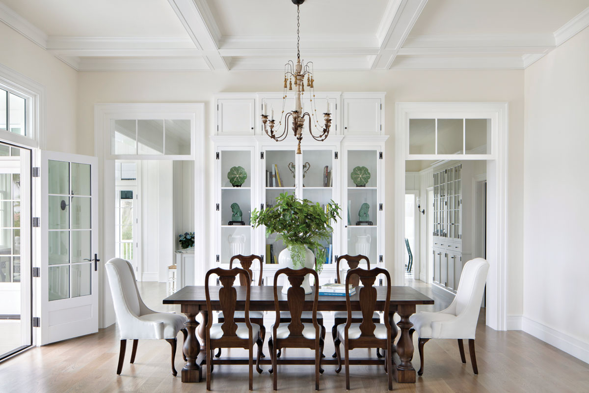 "Hickory Chair's upholstered seating plays host in the dining room, where Restoration Hardware's dark wood table easily obliges a party of eight. Aiden Gray's ""Italian Wedding"" chandelier shimmers above. The large cabinet was designed by Litchfield and his team for the space."
