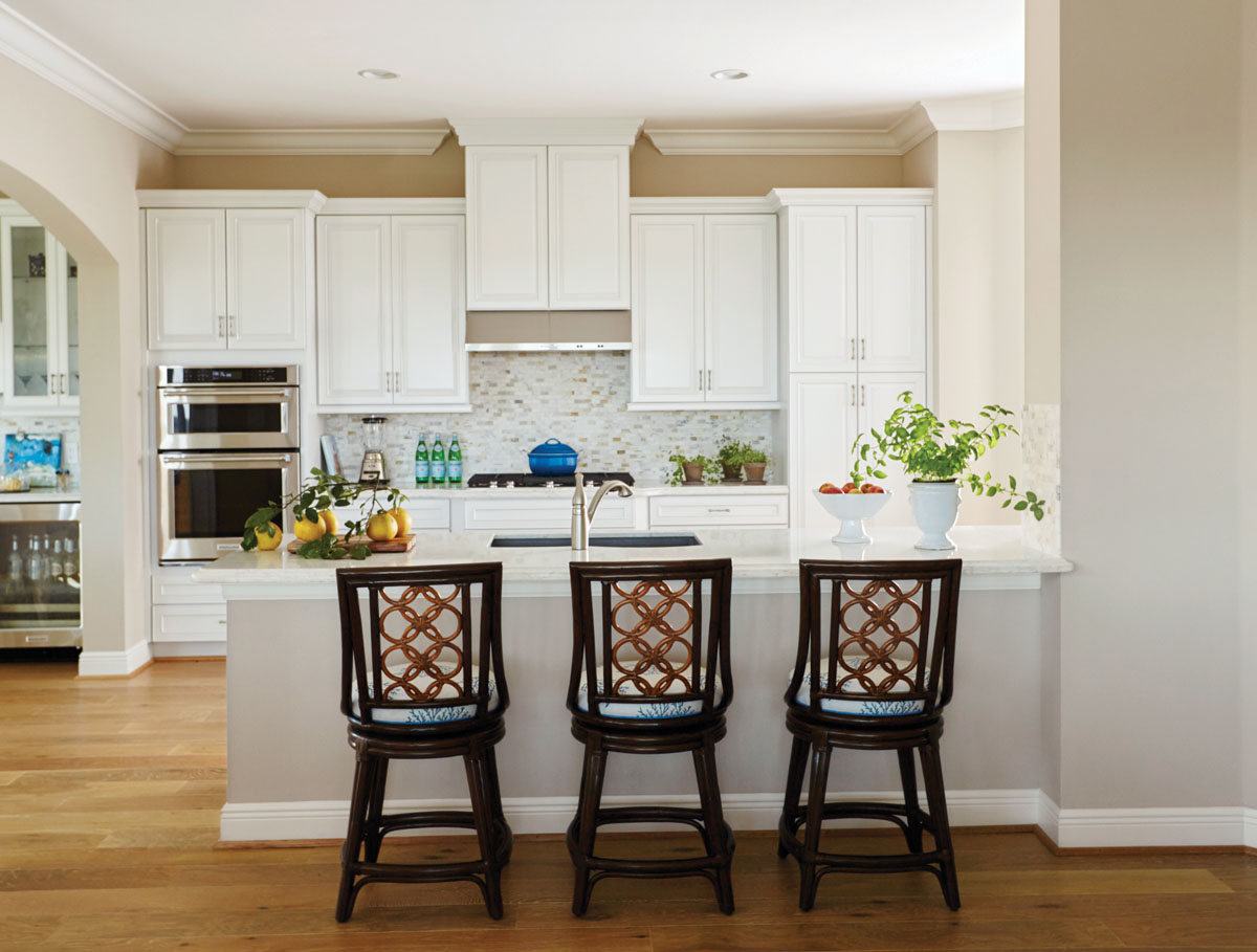 "Artistica's swiveling counter stools draw the eye into the kitchen. A delicate, blue coral reef pattern covers the seats while an intricate, tan rattan weave styles the back. ""The homeowners wanted to keep the kitchen simple and bright with just a touch of color,"" interior designer Pamela Harvey says."