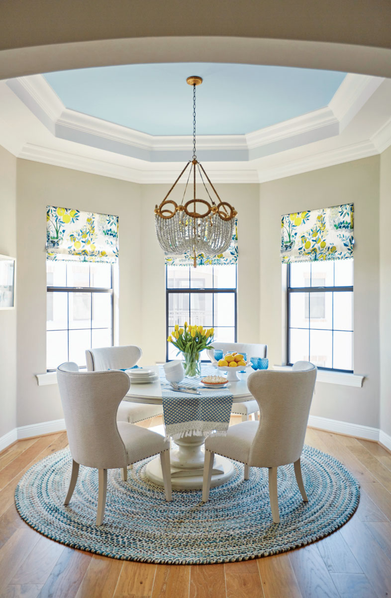 "Once used in a designer showhouse exhibition and deemed the ""star of the room,"" the Ro Sham Beaux light fixture in the breakfast area is so intriguing it's not to be ignored. Strands of white beads are draped together with swirls of gold paint to add a touch of glimmer. Beneath, chairs in white linen envelop an antique-white pedestal table sporting a curvaceous silhouette — both from Bernhardt."