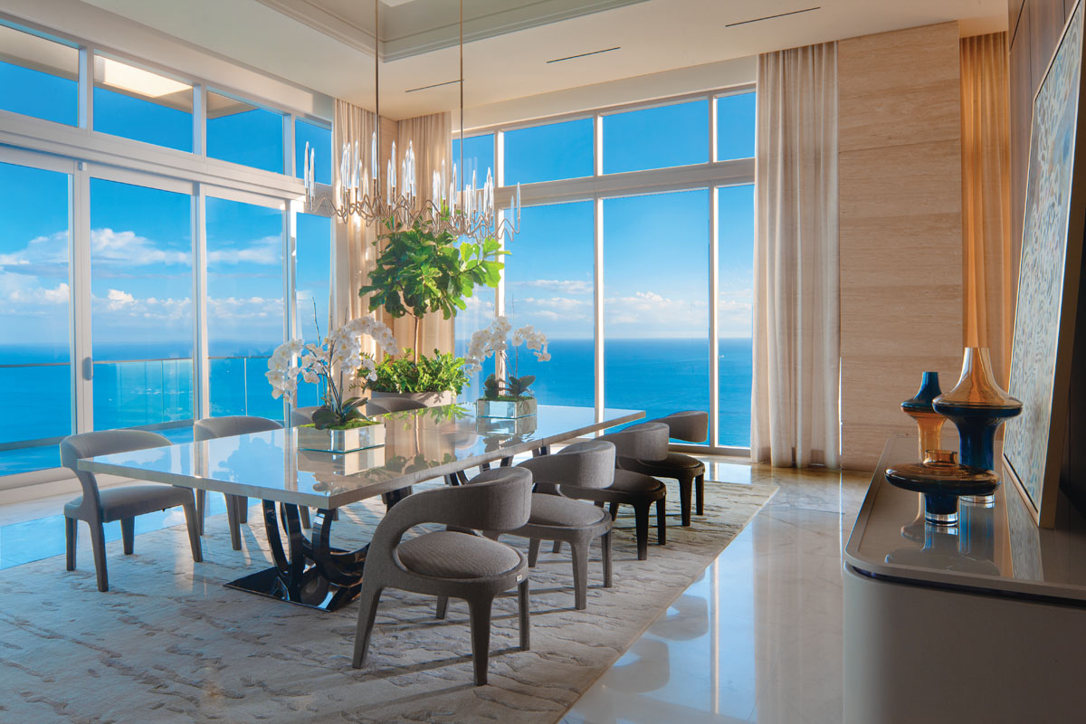 "In a spacious dining area framed by panoramic water views, the table topped in sumptuous sycamore wood is lined by Fendi Casa ""Berenice"" dining chairs that are open in the back and clad in taupe chenille with black details."