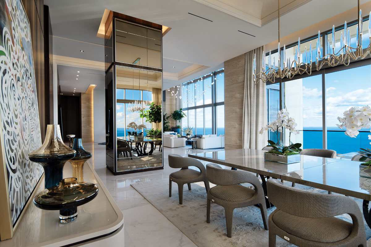 Sensation from Axiom Gallery provides an artistic touch delicately perched above Fendi Casa's modern sideboard in the dining area. Here, a pair of chandeliers resemble a constellation at night and connect well with the adjacent living area