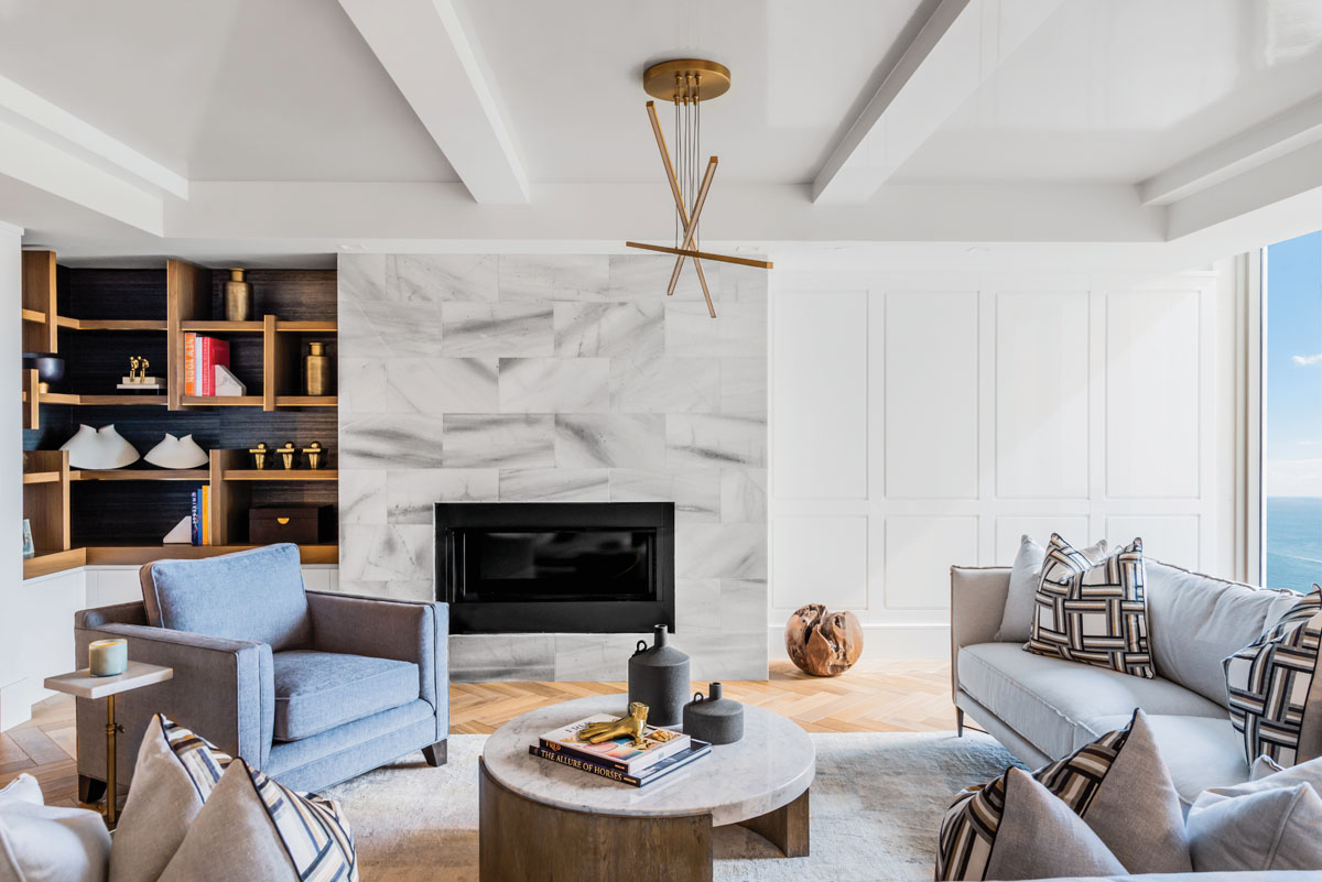 """Interior designer Wendy Berry orchestrated the living room furnishings in a casual choreography that spotlights the ocean views. """"For this room we brought the blue, gold, cream and black in,"""" she says. """"We did the muted colors of the outside on the Bernhardt sofas, but we brought in a lounge chair in Kravet's strong, blue chenille to anchor the setting."""""""