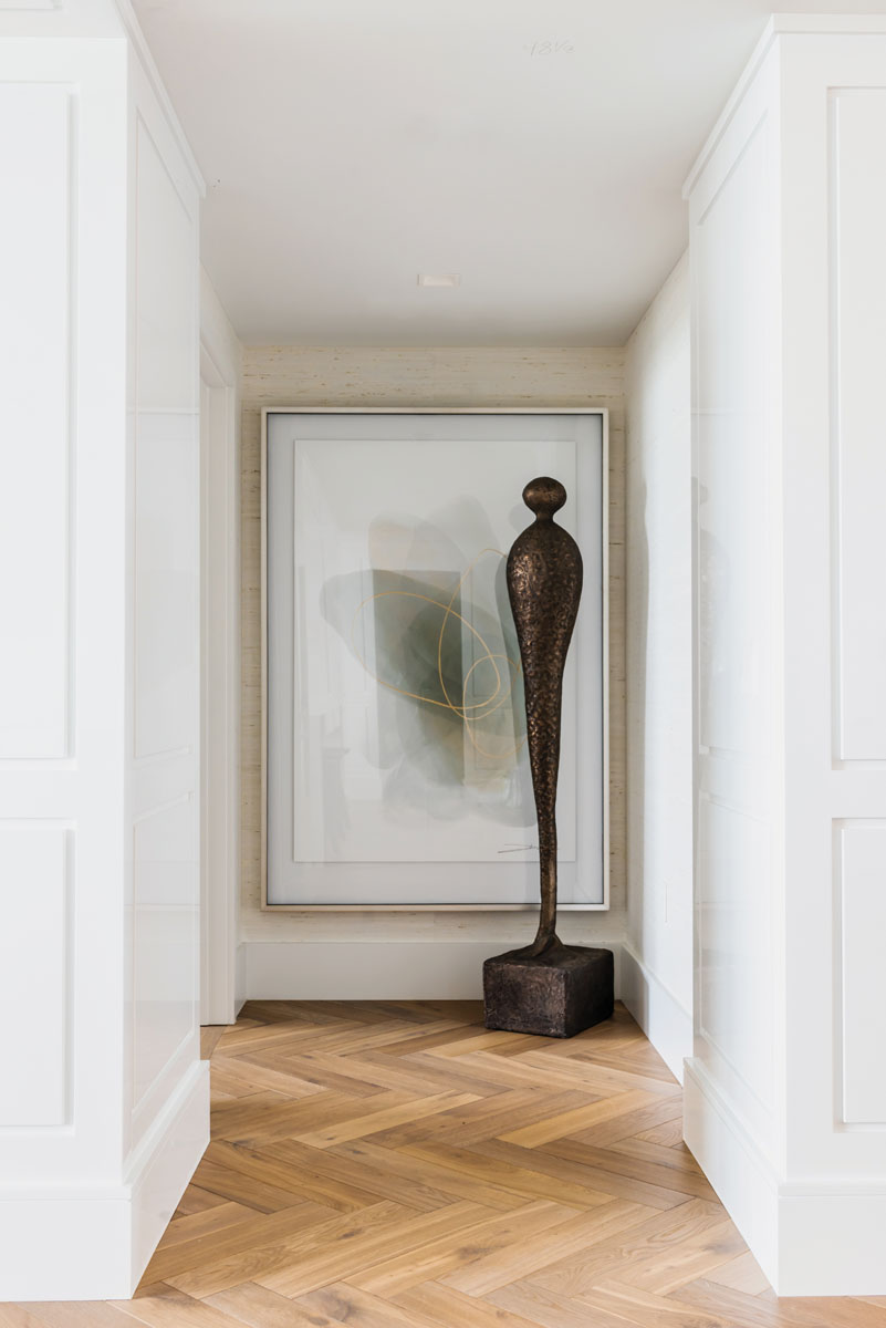 """""""The highlight of this art-filled hallway is actually the architectural detailing,"""" the designer says. """"It just made the place feel more like a house … it gives that unexpected separation."""""""
