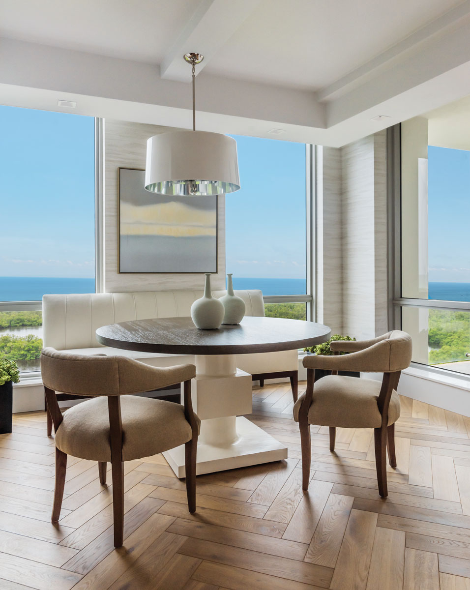 An expanse of windows brings the seaside front and center in the breakfast area. Here, a freestanding Theodore Alexander banquet joins a pair of Brownstone Furniture chairs at Bernhardt's rift oak table atop a white modern plaster base. Phillip Jeffries' wall covering mimics the horizon beyond.