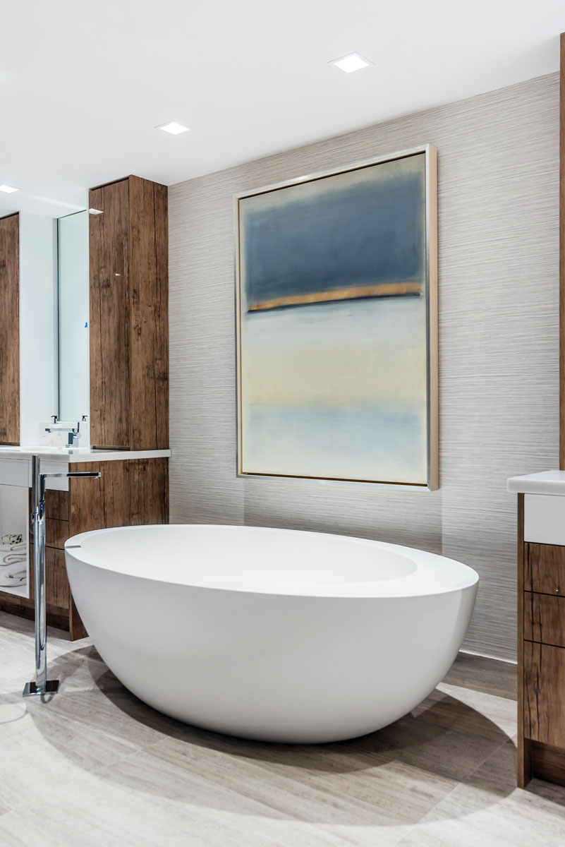 Resurrecting the dark and light juxtaposition, the luxurious master bath features MTI's white Cascara freestanding deep-soak tub surrounded in neutral tones further warmed by rich wood finishes.