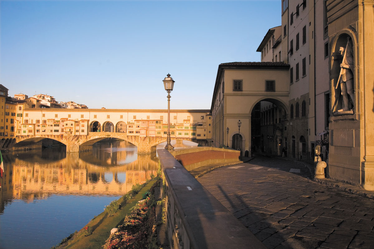 As the sun sets on the Arno River, guests savor the stunning view from the Ponte Vecchio, Florence's signature arch bridge, that can be seen from the hotel's exclusive open-air terrace. Photography by Richard Waite.