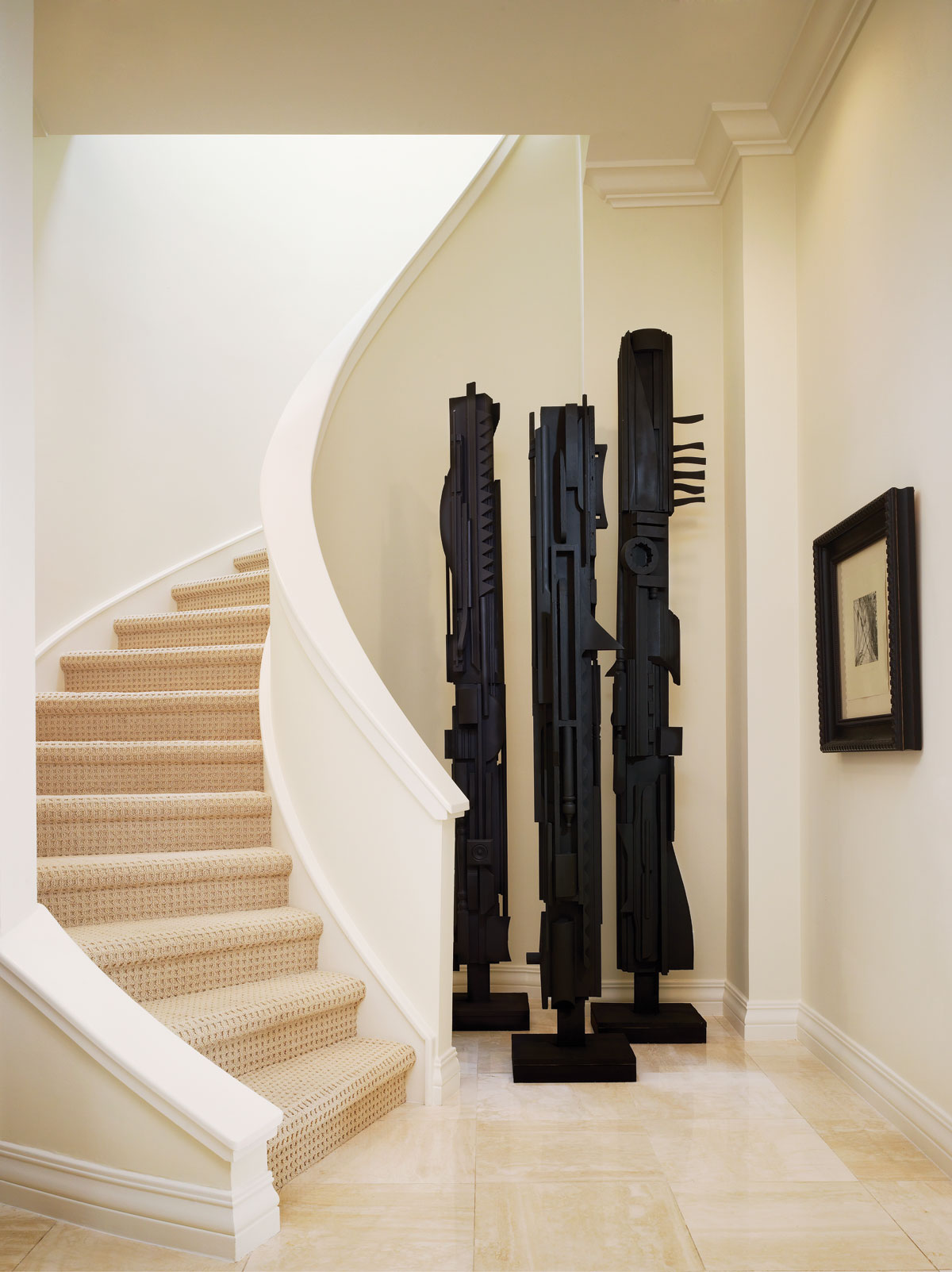 "American sculptor Louise Nevelson's totems make a bold statement in the stairway hall that opens onto a grand foyer. ""Here, we did what we do best,"" interior designer Jack Fhillips says. ""We mixed classic upholstered pieces with some traditional furnishings, contemporary art and antiques."""