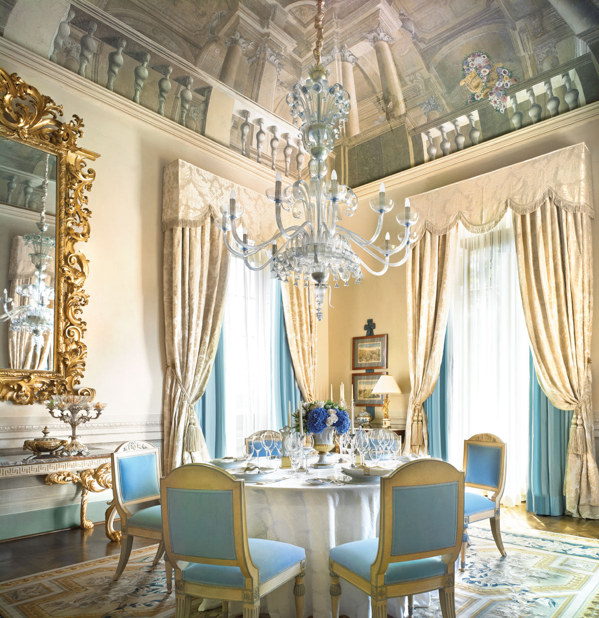 In The regal Royal Suite, an elegantly appointed dining room with a soaring frescoed ceiling comfortably seats eight.