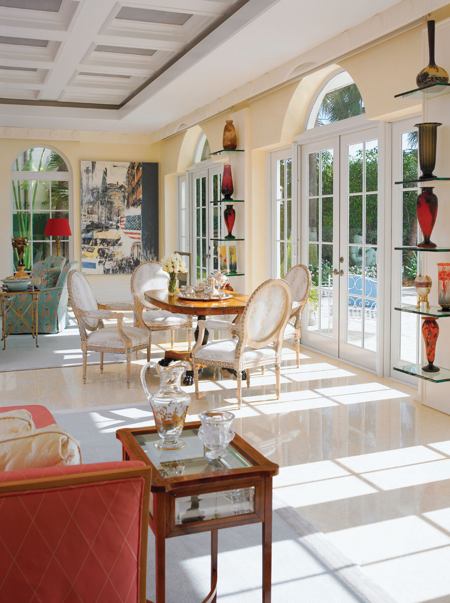 Floating-glass, back-lit shelving in the living room provides a dramatic showcase for the homeowner's collection of art glass, including pieces by Lalique, Daum, La Verre Francais, Emile Gallé and Loetz from Valerio Antiques.