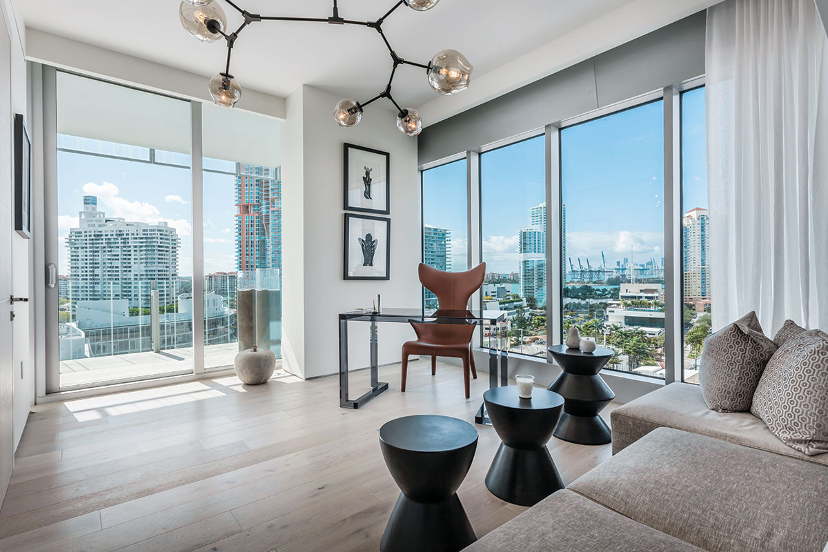 Sweeping views of the city and skyline take center stage in the light-filled office arranged with low-profile furnishings that do not detract from the scenery. Three shapely side tables from Cudesso for Curated Living can be easily moved to accommodate a silk chenille sleeper sofa in a taupe hue that is perfect for impromptu overnight guests.