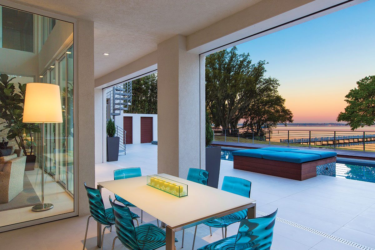 A favorite indoor-outdoor space, the lanai is designed with a dining table surrounded by vibrant blue Lucite chairs by Calligaris that are in perfect position to view the sun set over the river.
