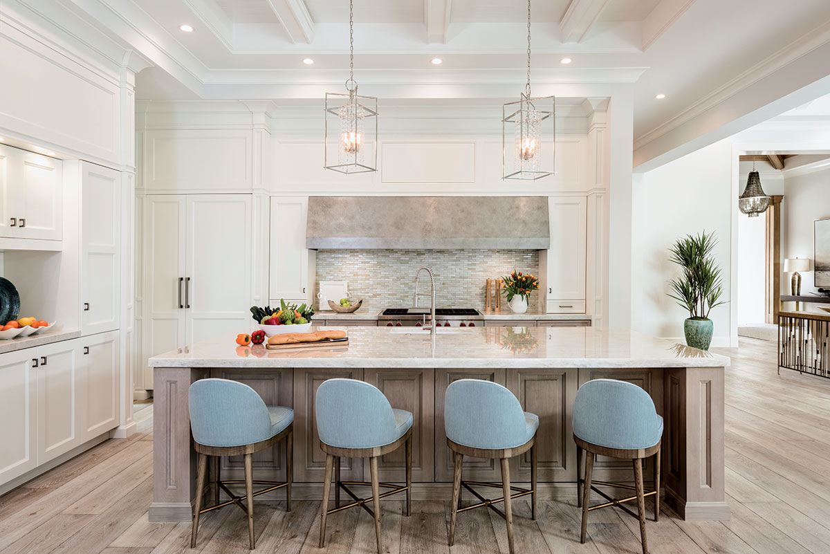 In the sleek, clean-lined kitchen, counter stools from Hickory Chair clad in a blue Sunbrella fabric pull up to the center island, finished in soft dove gray with a stunning two-inch Cristallo quartzite top. Twin sparkling polished nickel pendants from Hudson Valley provide the perfect finishing touch.