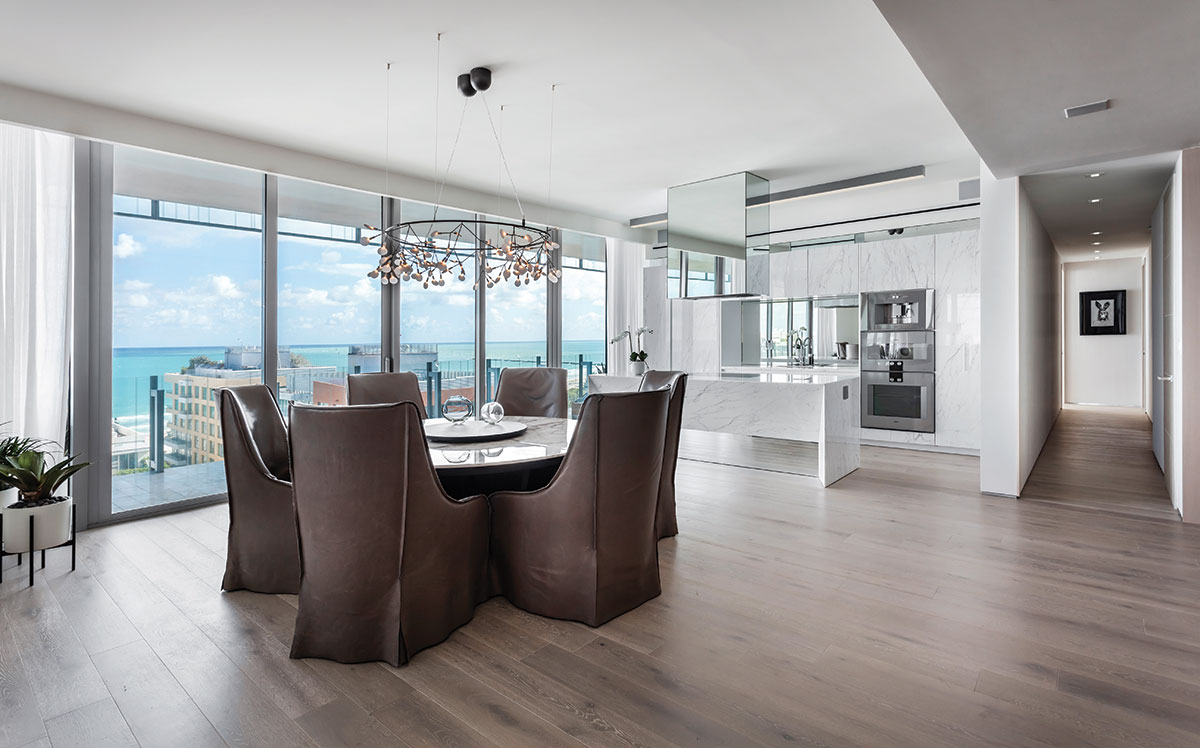 In the dining area, mushroom-colored leather-clad chairs from Verellen create a dramatic contrast near a bright kitchen with white-veined marble cabinetry. A Bertjan Pot for Moooi chandelier from Planet Lighting glitters above Maxalto's marble table enhancing the ocean view through floor-to-ceiling windows.