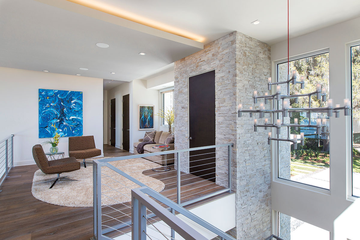 "Upstairs, an intimate sitting area is defined by a shapely area rug. ""Nemo,"" from YLighting, is a modern interpretation of a classic candle chandelier, that suspends stylishly from the two-story ceiling."