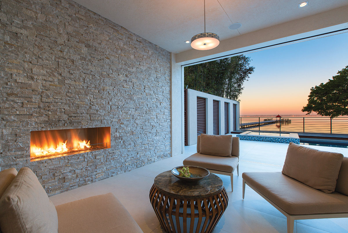 n another area of the lanai, family and friends get cozy on chairs from Brown Jordan that are positoned to enjoy a custom-designed fireplace with a stone wall crafted by Ferid Marble & Tile.
