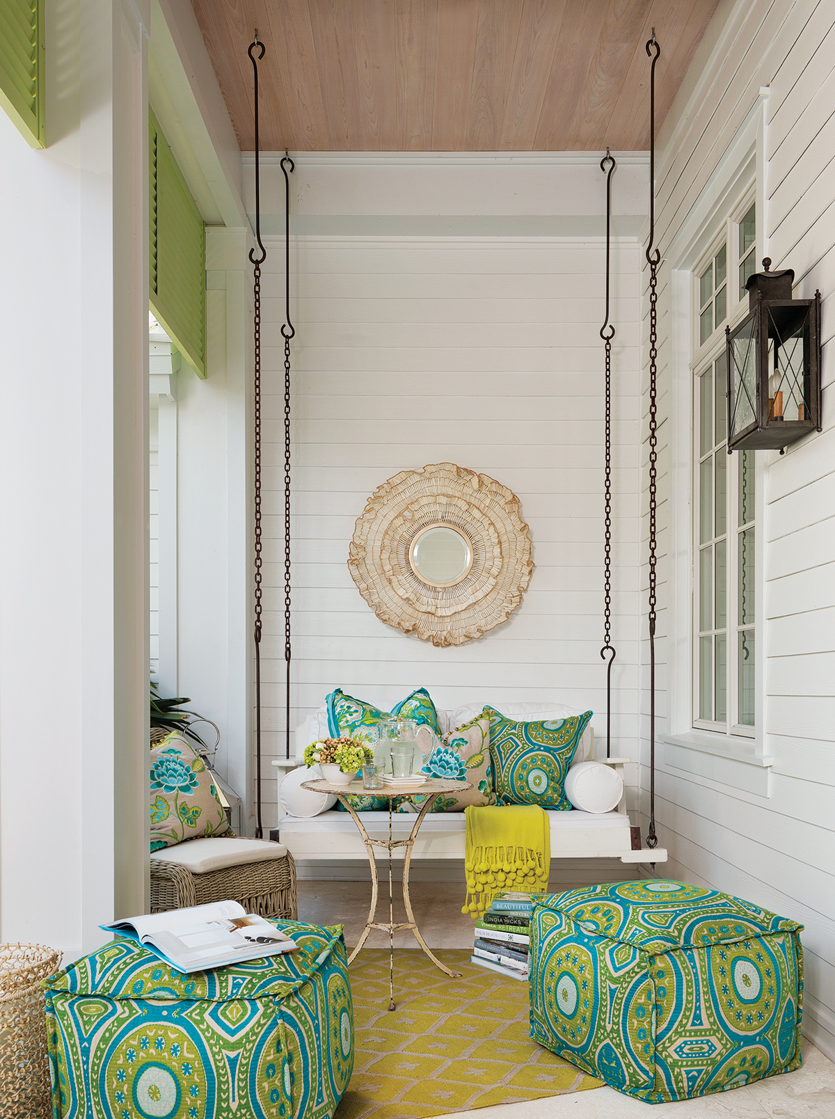 Bright patterned fabrics in ottomans and accent pillows continue outdoors on the cozy front porch. A rattan mirror from Palecek and a vintage bistro table convey an earthy vibe, while ottomans clad in a chartreuse-and-turquoise print provide extra seating.