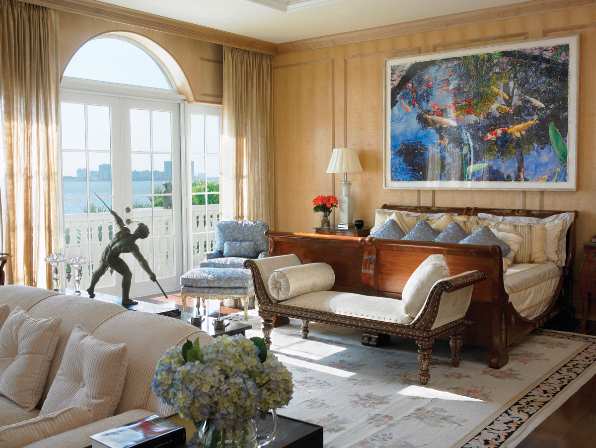 Pond by Joseph Raffael hangs above a sleigh bed that is actually two antique twin beds joined together. A settee from John Rosselli rests at the foot of the bed. In the master bath, above, a copper bench pairs with an antique chair reupholstered in Pollack silk.
