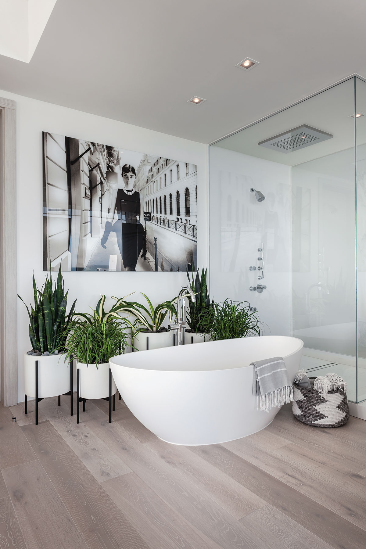 "A large black-and-white photograph of Audrey Hepburn by photographer Axel Crieger keeps watch in the master bath over a vessel tub, a ""rain"" shower and a collection of lush plants."