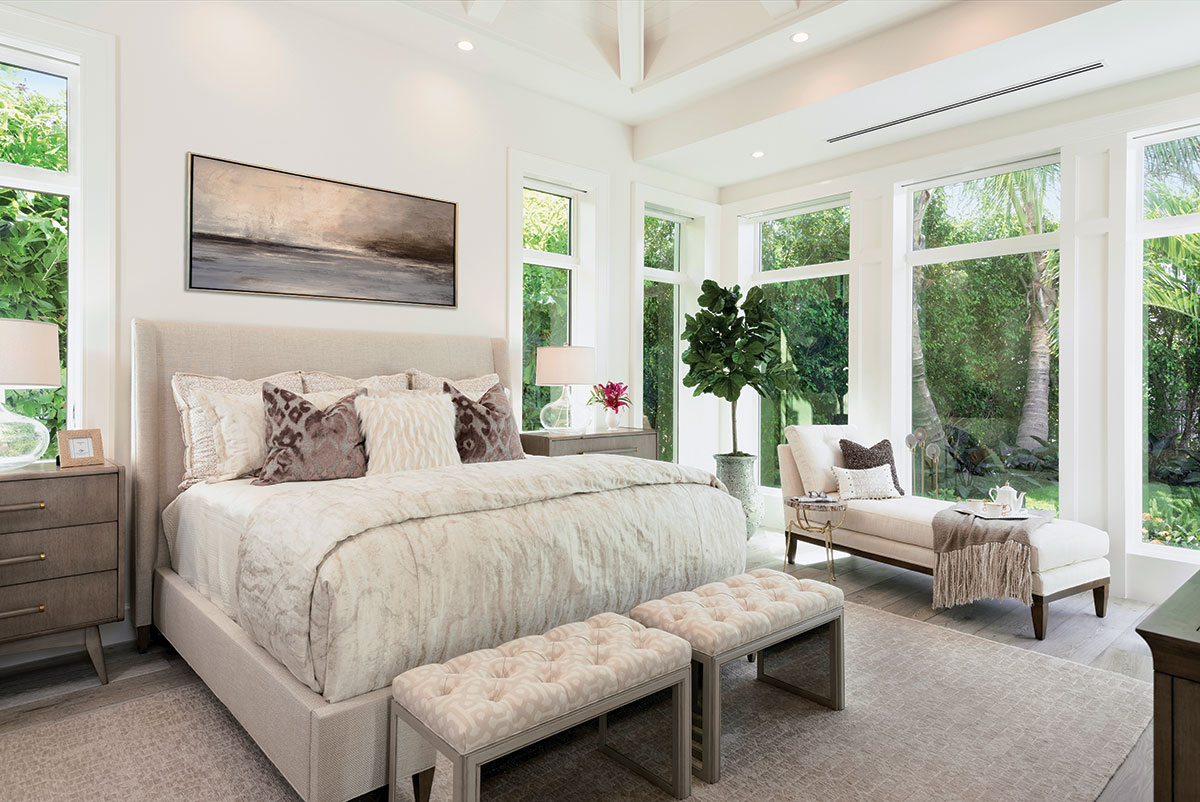 An expansive view from large windows adds a layer of tranquility to the spacious master bedroom designed in neutral tones. Fronting Hickory Chair's king size bed are Vanguard's ivory-beige tufted ottomans.