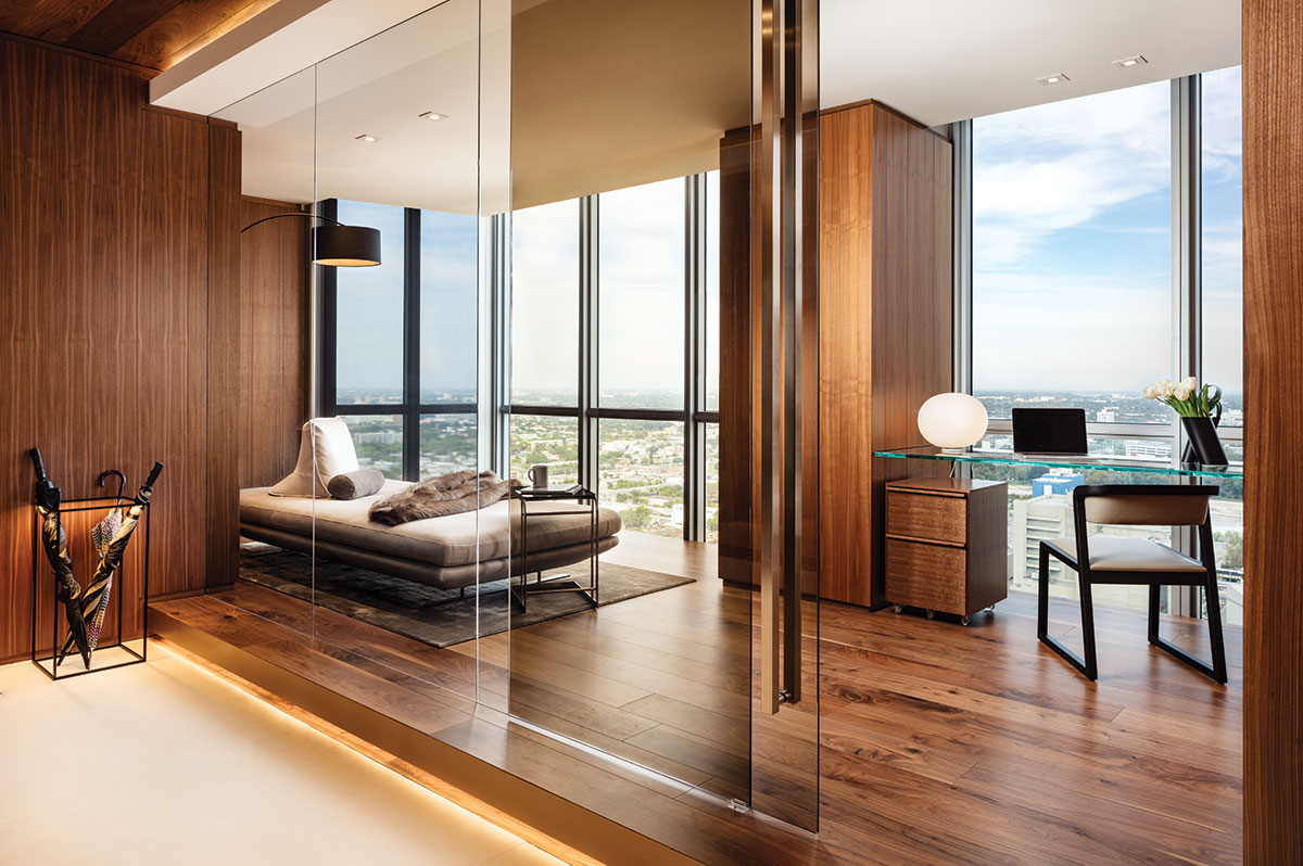Just off the entryway to the master suite, a bronze glass wall by Val Glass & Mirror slides open to an inviting study that doubles as a guest room. Here, a plush throw from Restoration Hardware tops a Ligne Roset chaise that provides the perfect spot to relax and enjoy the views.
