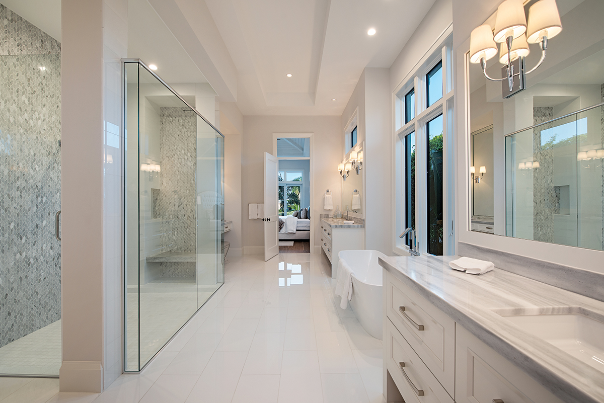 Clean lines, polished tile flooring, an expansive shower, and white vanities topped in Rain Forest Marble's pearl gray striation opens up the master bath. A picture window with lush garden views provides the perfect backdrop for the Victoria & Albert tub from Ferguson.
