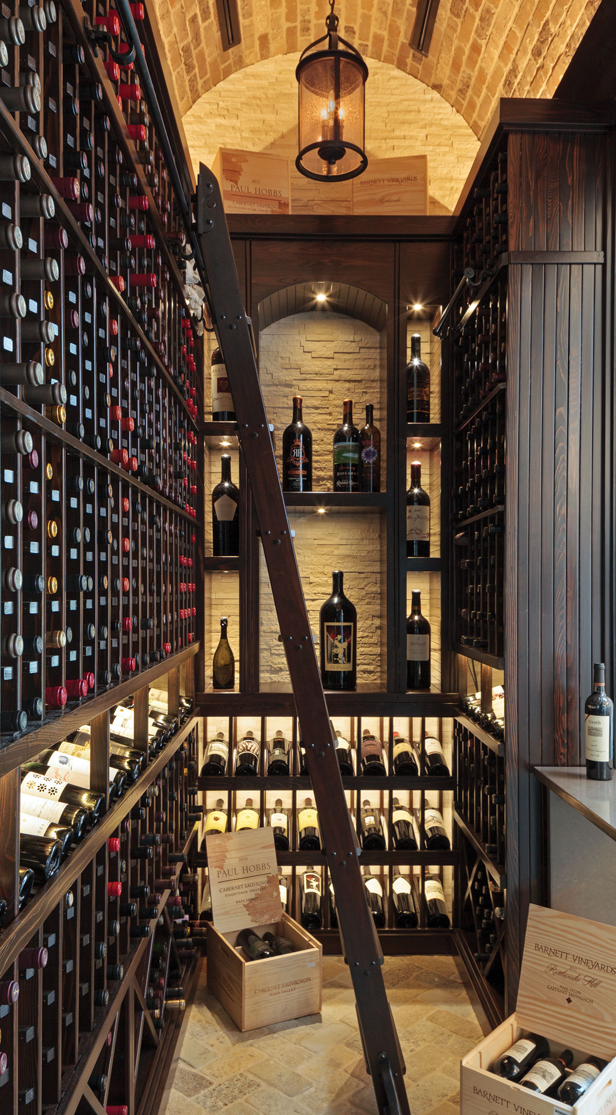 "In the wine room, the designer used uplighting for the ceiling, a chandelier for ambiance and low voltage lighting for each shelf. ""We used brick and dark wood inside, with chipped, split-faced stone on the back wall,"" DuPont says."