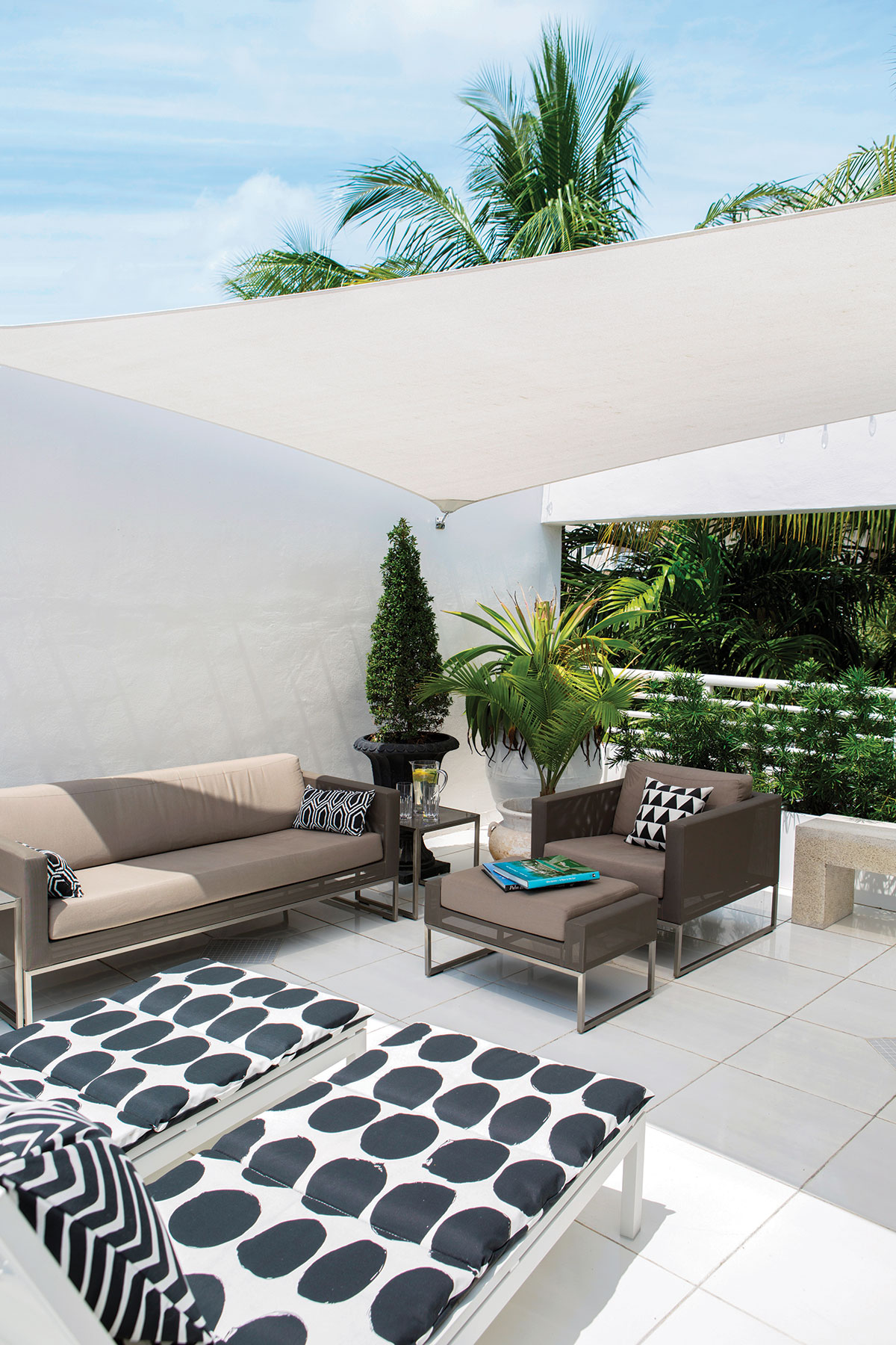 Bolder in execution, the third-floor terrace repeats the interior scheme. Crate & Barrel's sofa and armchair shape a social grouping, while the owners' chaise lounges recline nearby. Large flower pots and planters are olive jars Garger had shipped from Greece.